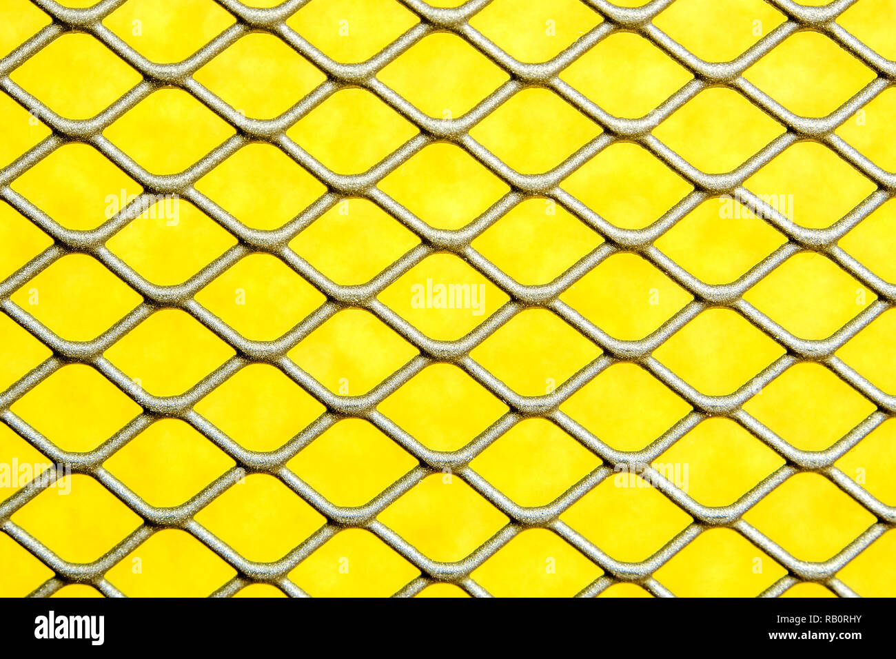 closeup of silver grey colour metal wire mesh fence with golden background shade Stock Photo