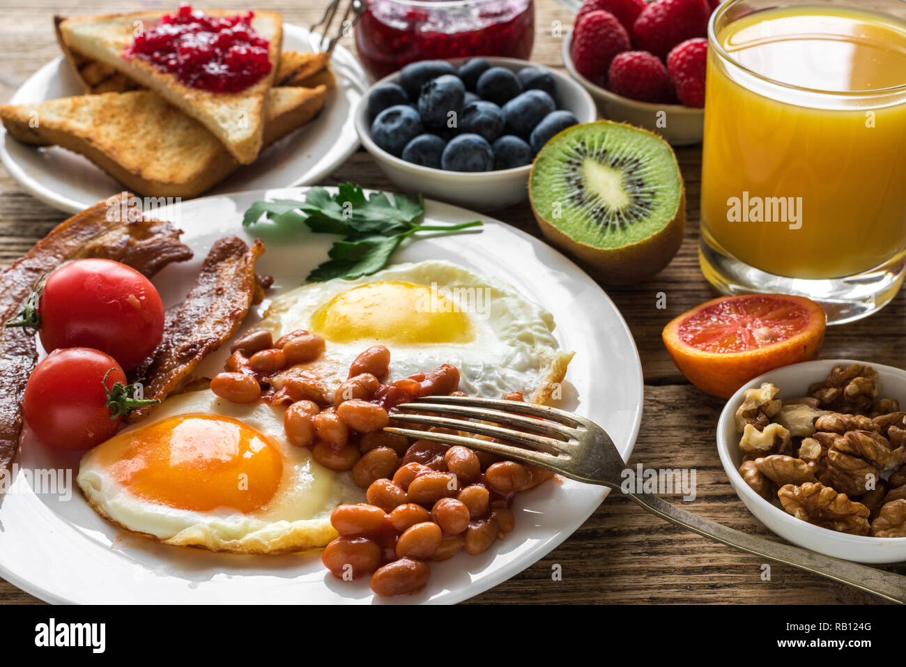 English breakfast served with fried egg, beans, tomatoes, orange juice, bacon and toast with nuts, fresh fruits and berries. close up - Stock Image