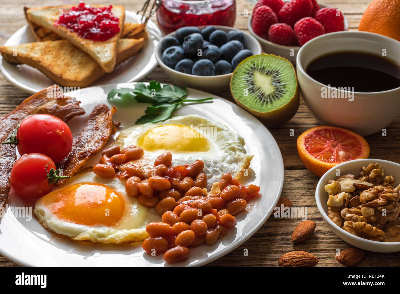 English breakfast. fried egg, beans, tomatoes, coffee, bacon and toast with nuts, fresh fruits and berries. close up - Stock Image