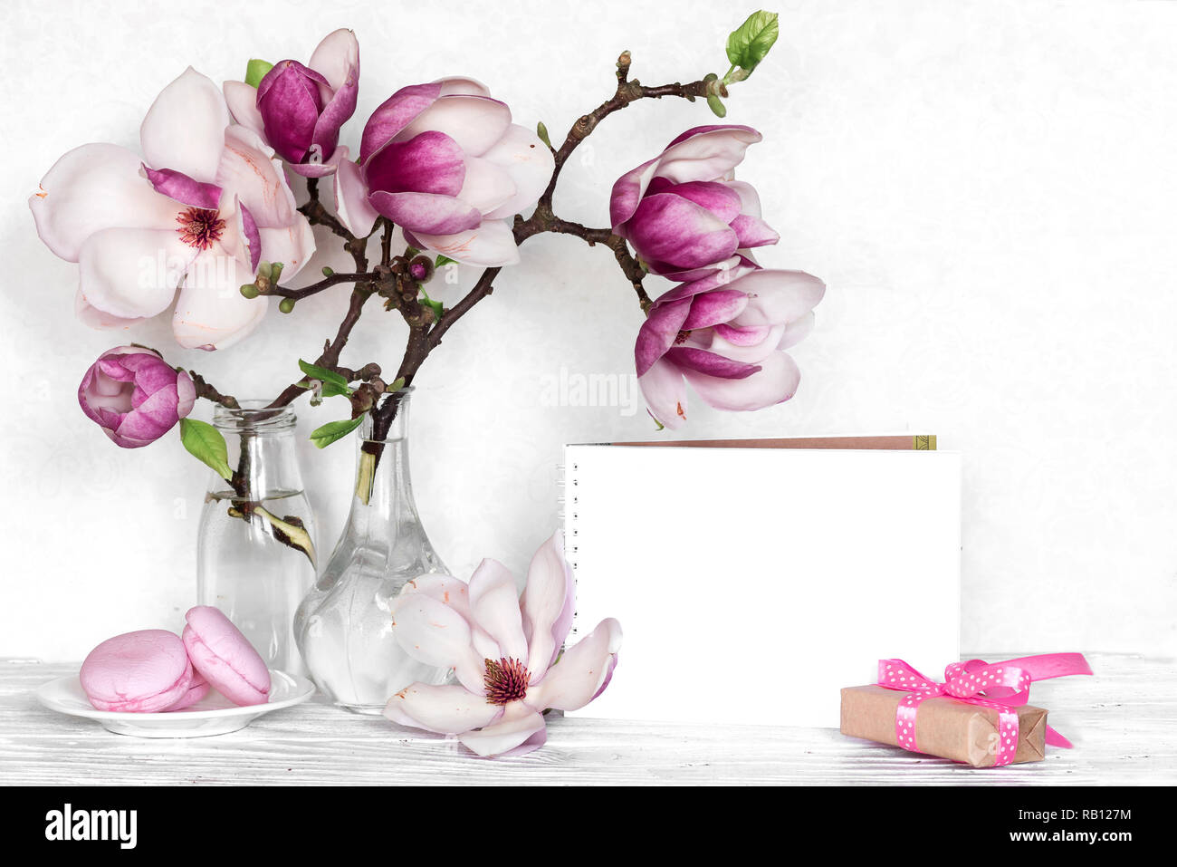 Creative layout made with pink magnolia flowers, empty card, macarons and gift box on white wooden background. mock up. still life. wedding frame. spr - Stock Image