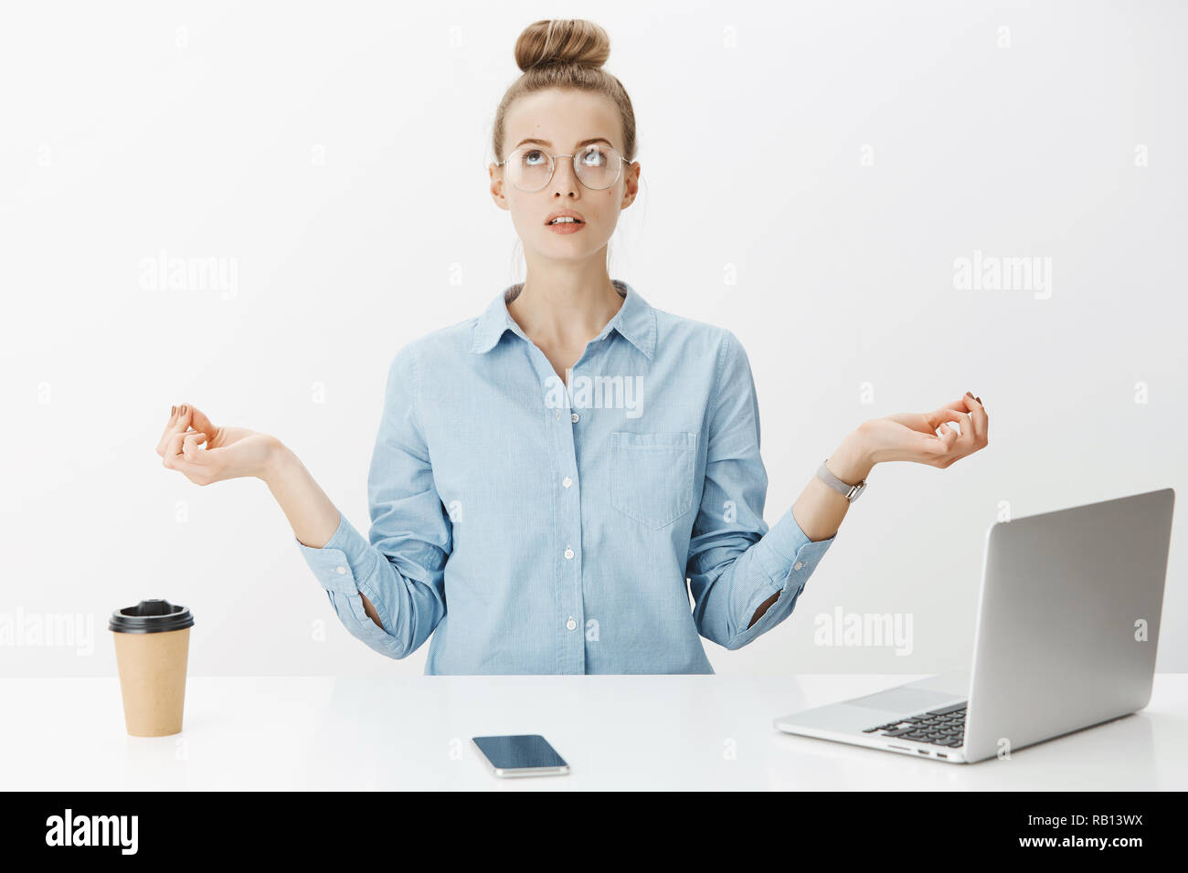 Woman Meditating In Office Sitting Near Table Having Break From Writing Article In Laptop Drinking Coffee