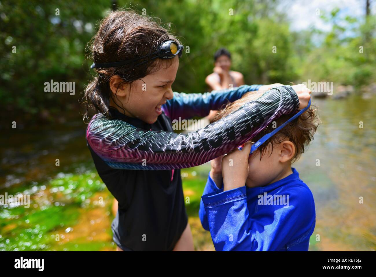 A mother watches her children swim in a stream, Alligator Creek, Townsville, Qld, Australia Stock Photo