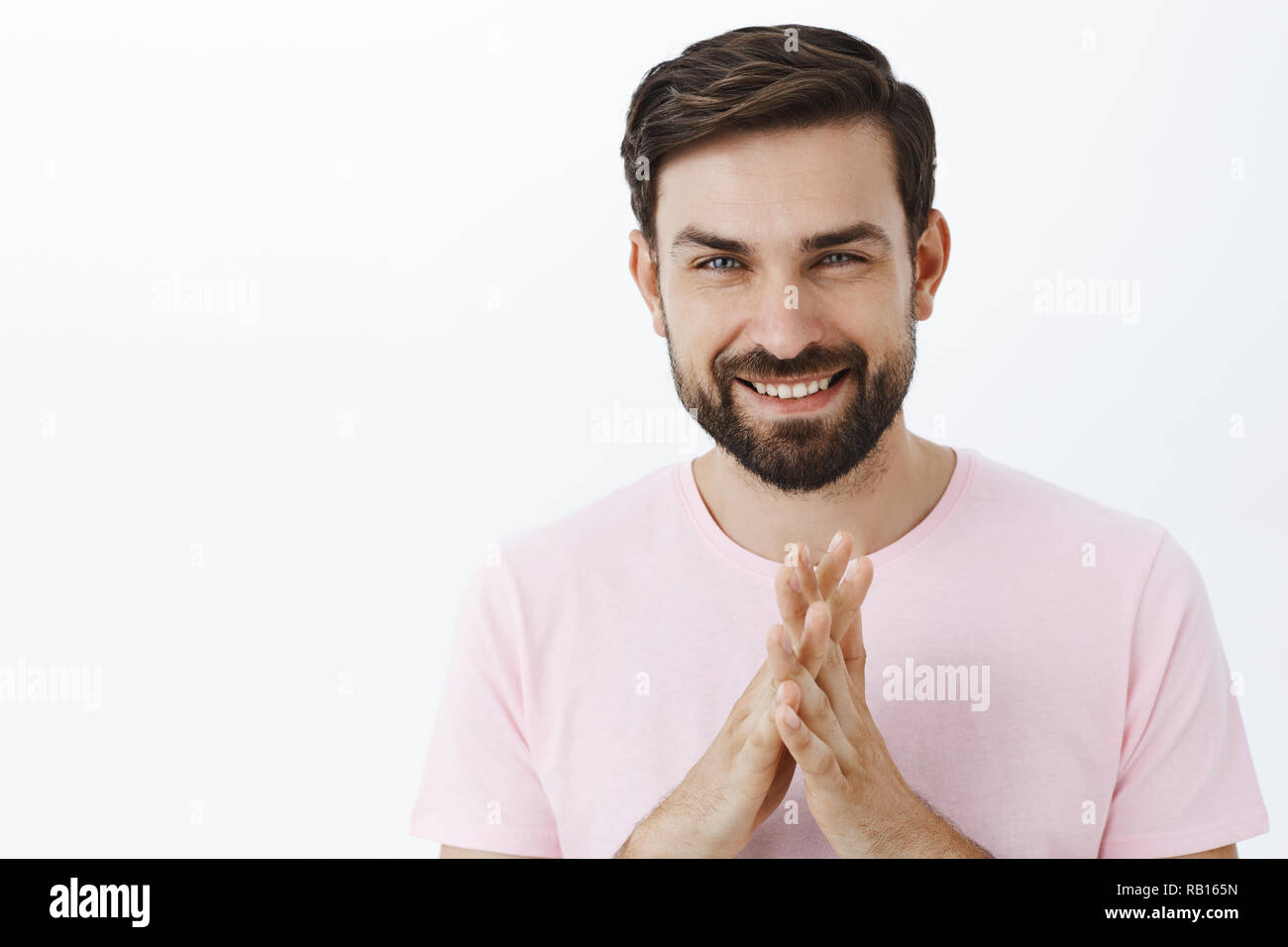 Guy have excellent plan will show how business makes. Handsome smart and creative intelligent caucasian male with beard rubbing palms and smiling delighted having perfect idea over gray wall - Stock Image