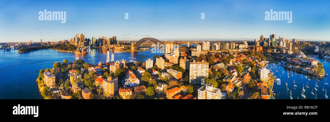 Wide aerial panorama over rooftops of residential buildings in Kirribilli suburb of Sydney with view from city CBD landmarks on harbour shores to Nort - Stock Image