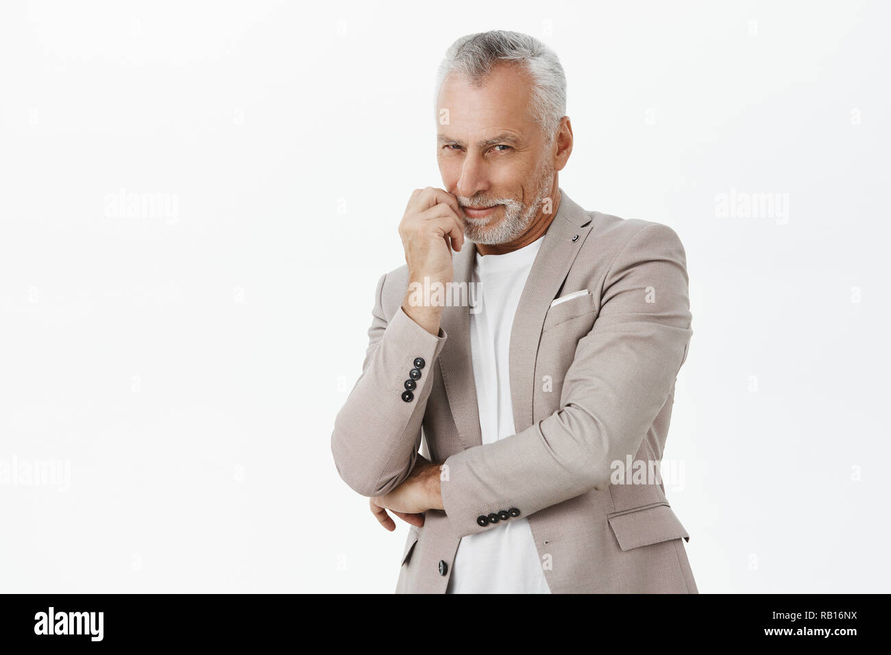 Smart and tricky enthusiastic old man with white beard and hair crossing hand against chest and touching lip smiling curiously and squinting from interest at camera having idea or intention - Stock Image