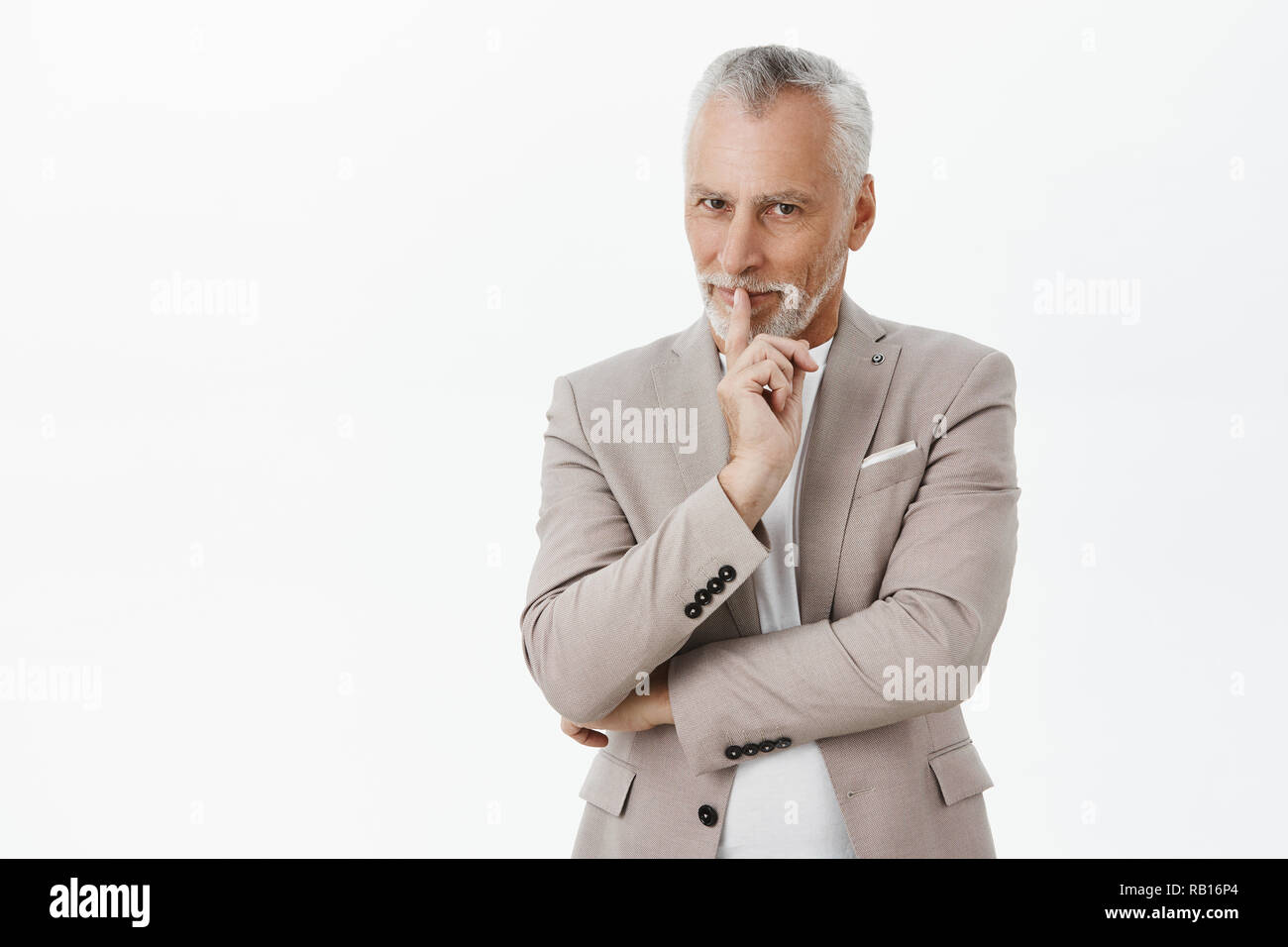 Enthusiastic and creative charming senior businessman with white hair and moustache in elegant stylish grey suit showing shh gesture with index finger over mouth smiling tricky having plan or surprise - Stock Image