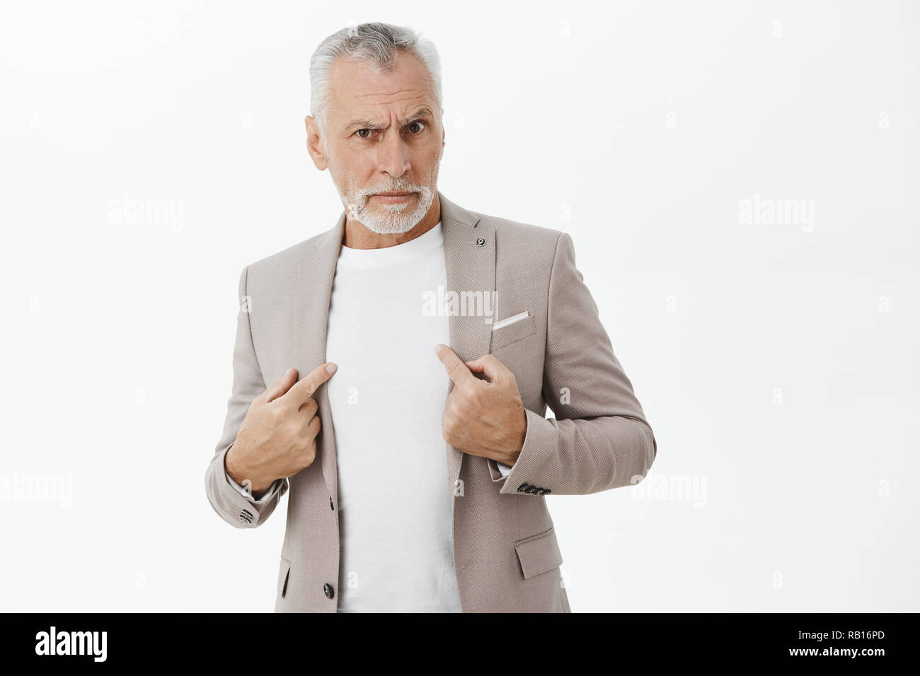 Portrait of senior man being accused in commiting crime standing insulted and intense pointing at himself with serious displeased and offended expression asking question at camera over gray wall - Stock Image