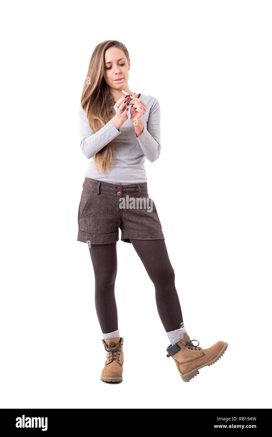 Candid unposed blonde young stylish woman rolling cigarettes. Full body isolated on white background. - Stock Image