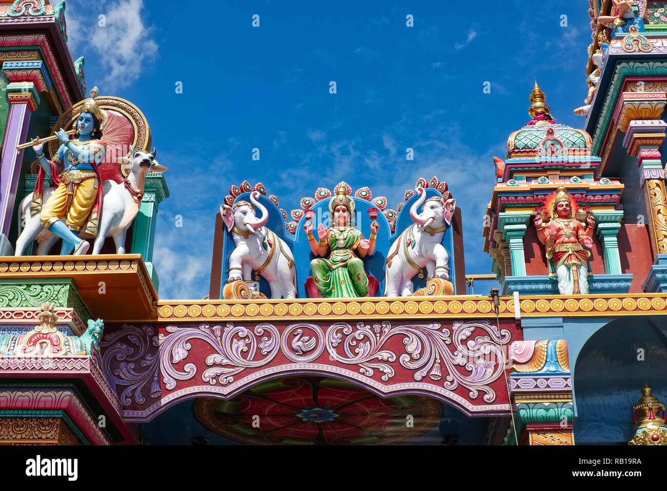 A partial view of the roof of Sri Vadapathira Kaliamman Temple in Serangoon Road, Singapore, with figures of Hindu deities, elephants and a cow - Stock Image