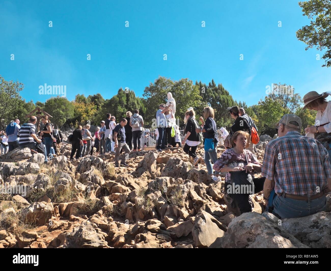View of the Virgin Mary on Apparition Hill in Bosnia & Herzegovina  during a bright summer day showing lots of people praying Stock Photo