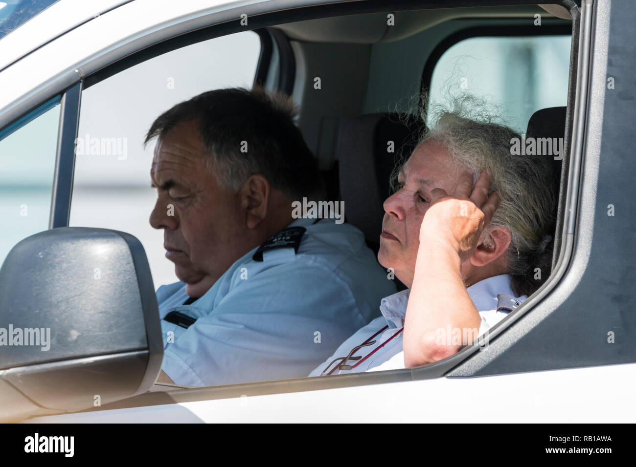 A couple of people looking bored and fed up, appearing to be parking wardens, sitting in a van seemingly looking out for victims, in the UK. - Stock Image