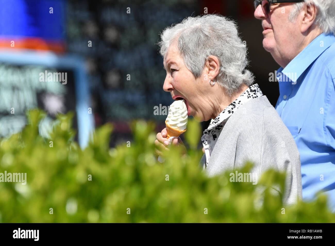 Senior couple walking on a promenade on a warm Spring day in the UK, eating ice creams. - Stock Image