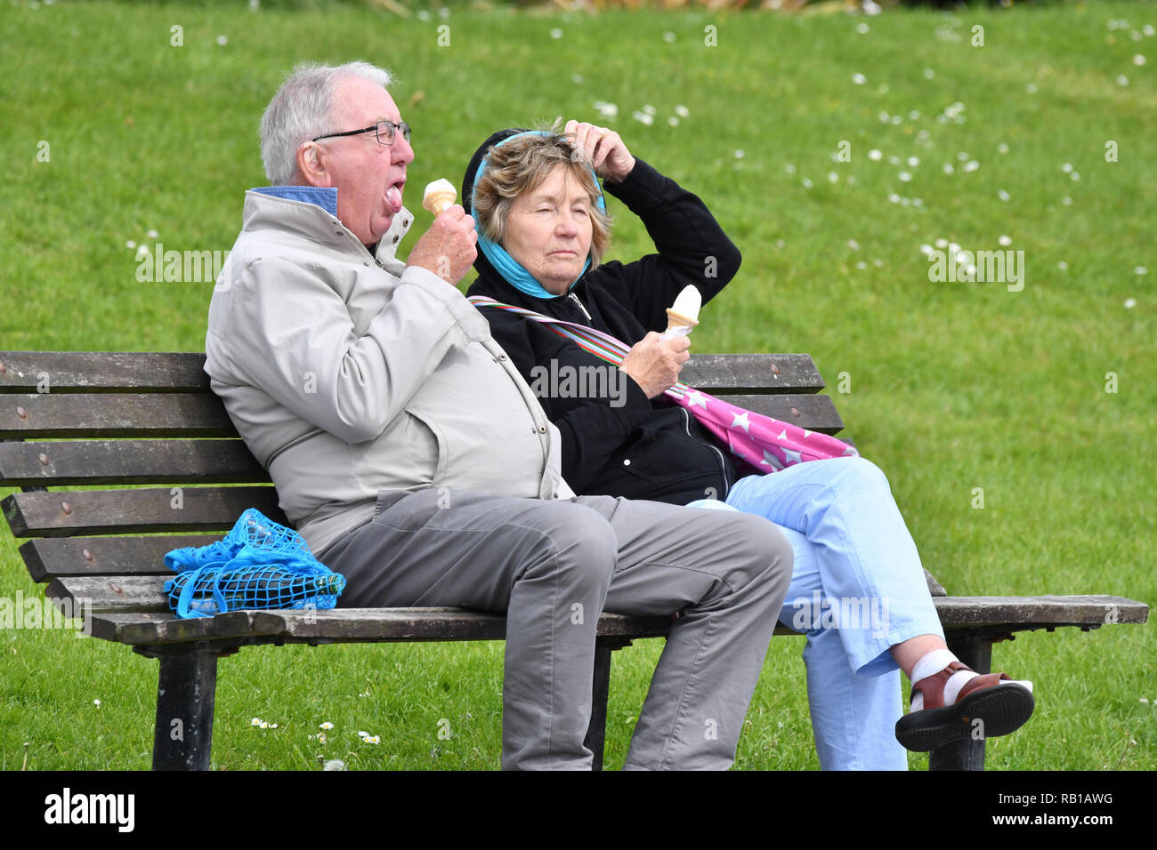Middle aged to elderly couple of people sitting on a wooden park bench wearing coats eating ice creams, on a cold day in Spring in the UK. - Stock Image