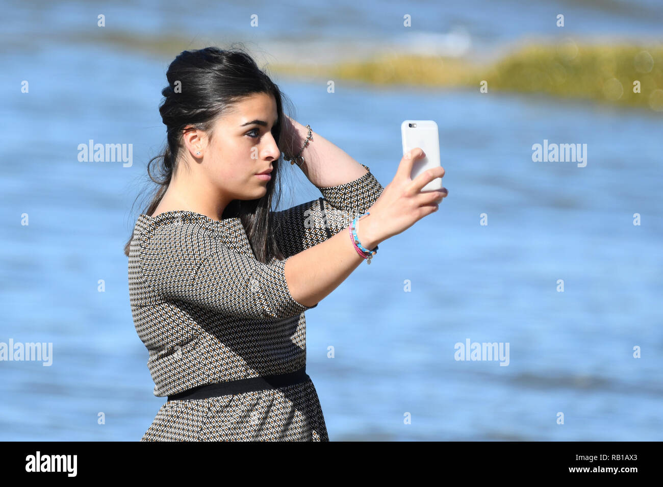 Young woman, teenager or early 20s, taking selfie photograph on a smartphone on a beach. - Stock Image