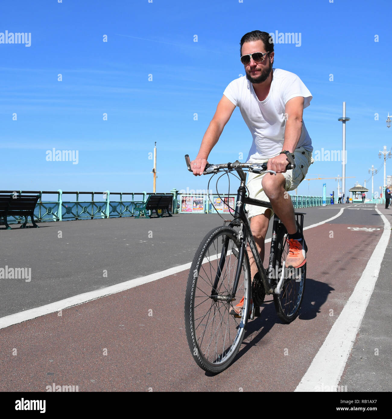 Man in 20s or 30s cycling along a cycle lane on the promenade in Brighton, East Sussex, England, UK. - Stock Image