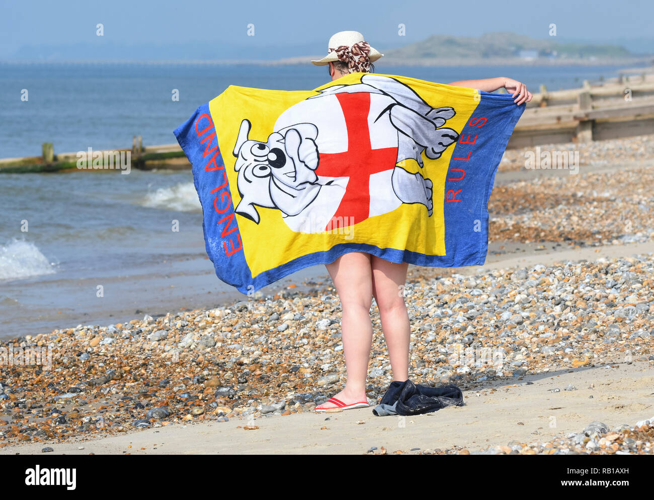 A woman dries off on a beach by the sea with a beach towel, on a hot day in Spring at a seaside resort in the UK. Stock Photo