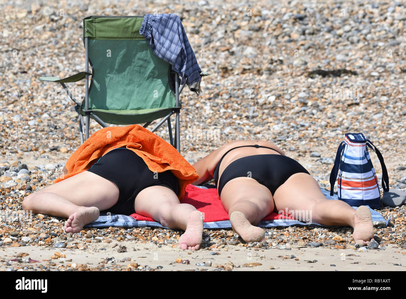 A couple of people laying face down on beach towels in swimwear on a beach, getting a sun tan on a hot day in the UK. - Stock Image
