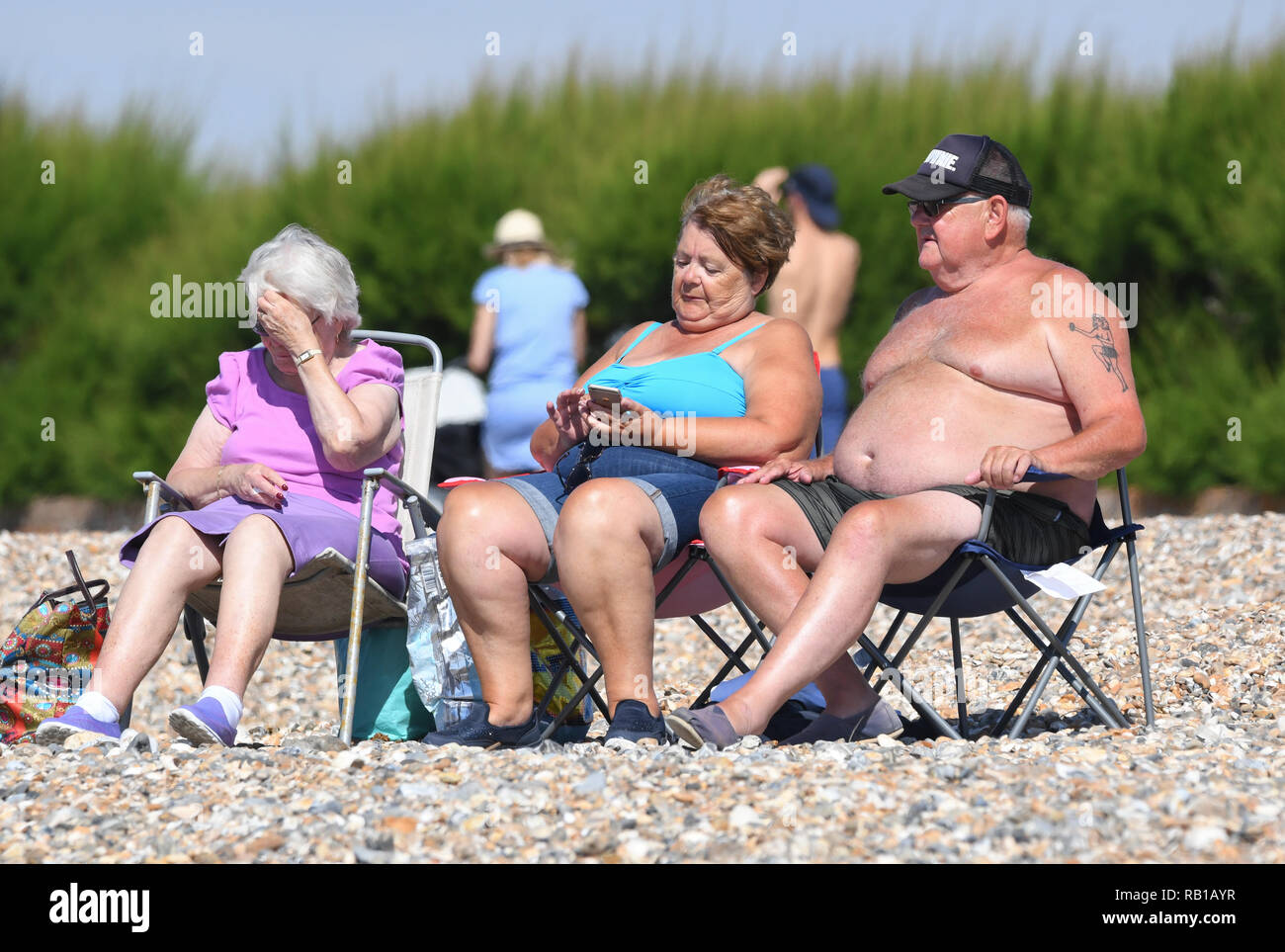 Group of people sitting in the sun on the beach on a hot day during the Summer 2018 heatwave in the UK. - Stock Image