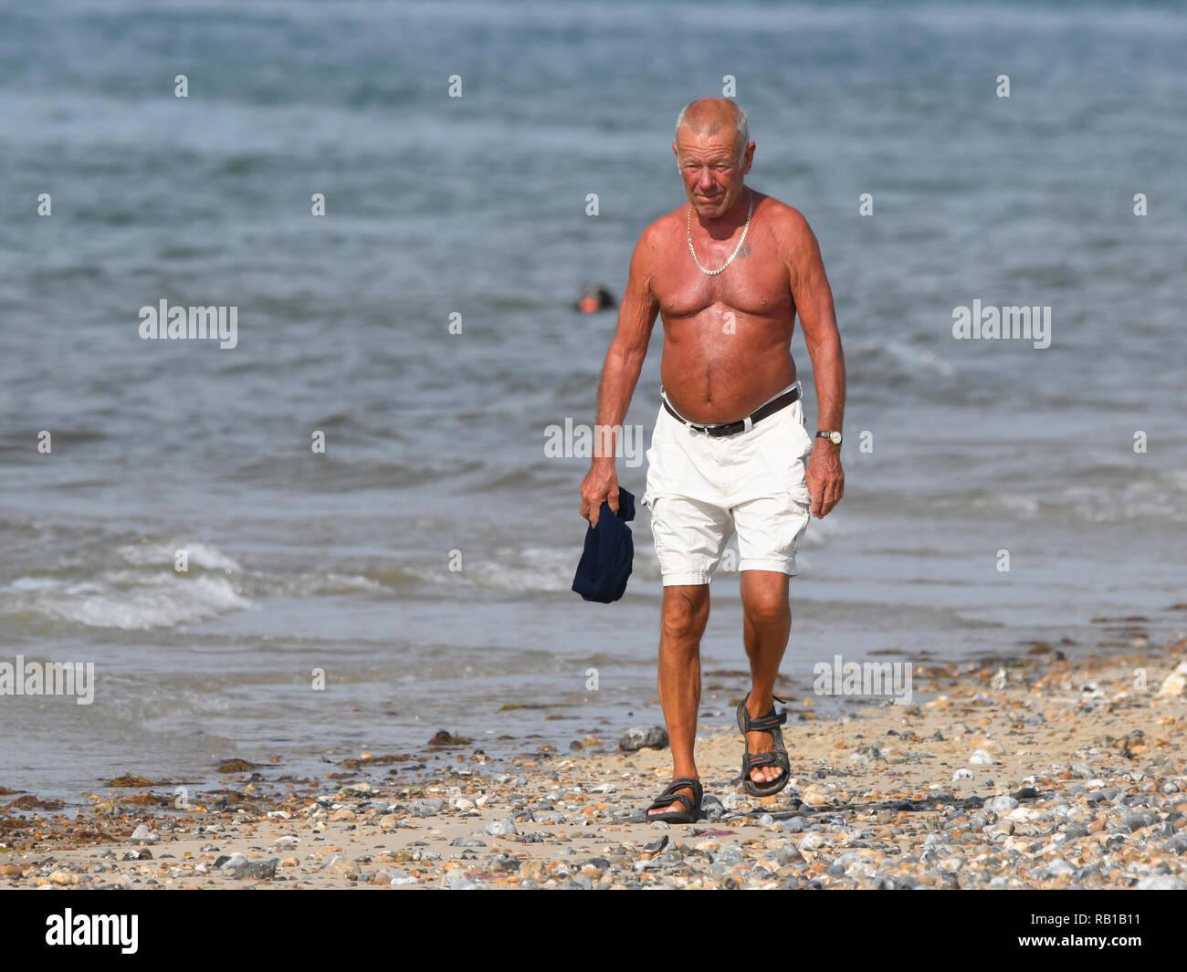 Shirtless man in 60s or 70s walking along the beach by the seafront on a hot Summer's day in the UK. - Stock Image