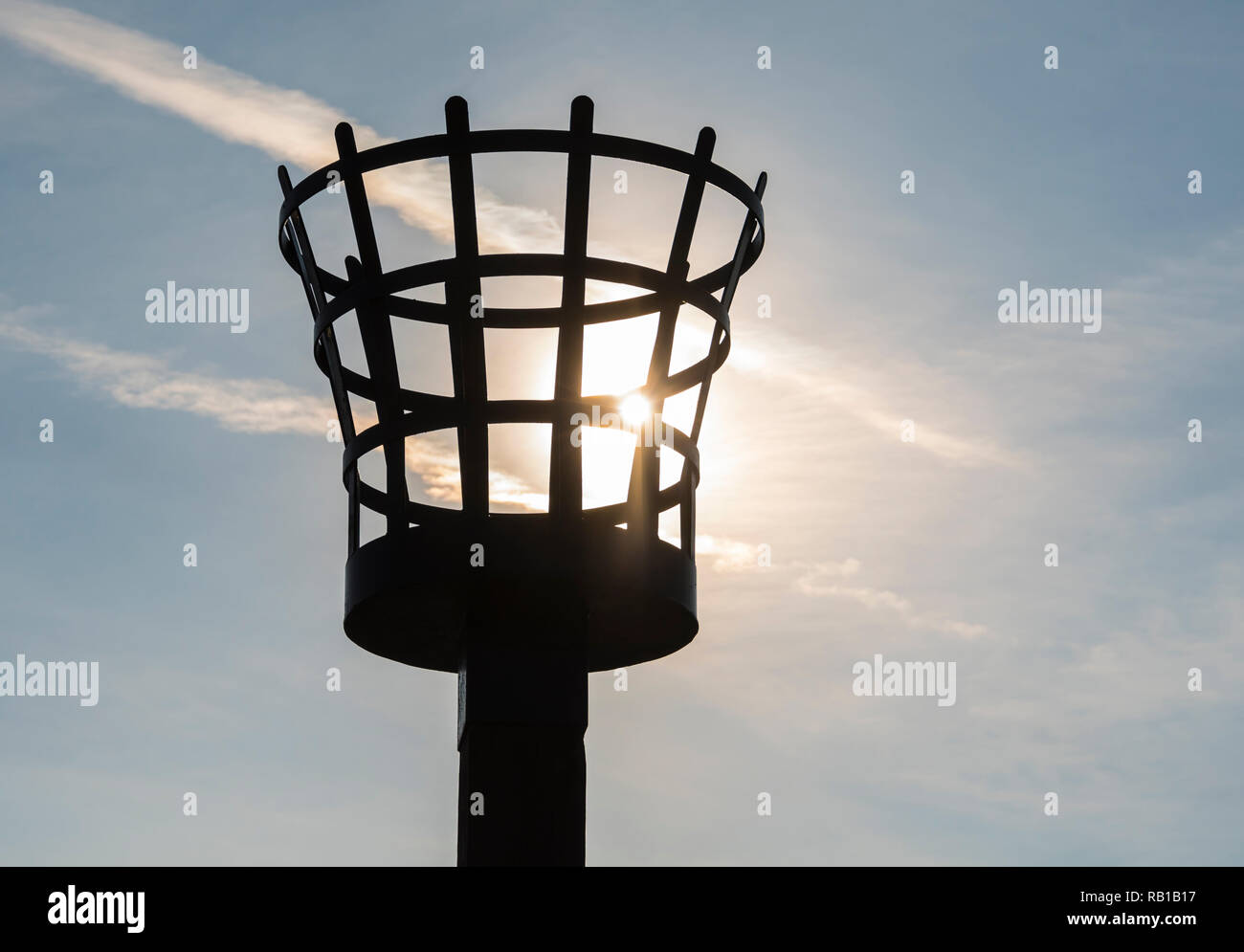Sun shining through a beacon brazier by the coast in the UK. - Stock Image