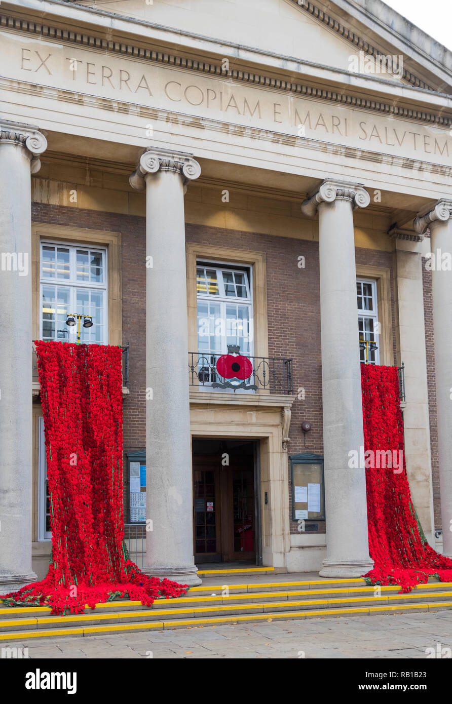 Display of poppies draped over balconies outside Worthing Town Hall for Remembrance Day 2018 in Worthing, West Sussex, England, UK. - Stock Image