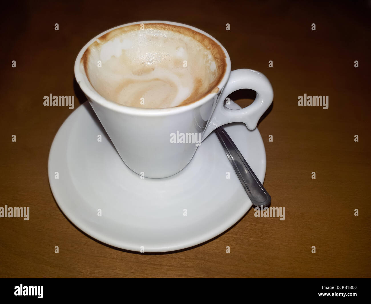 A white and fulfilled cup of coffee over a saucer with a teaspoon beside it and a darken woody background - Stock Image