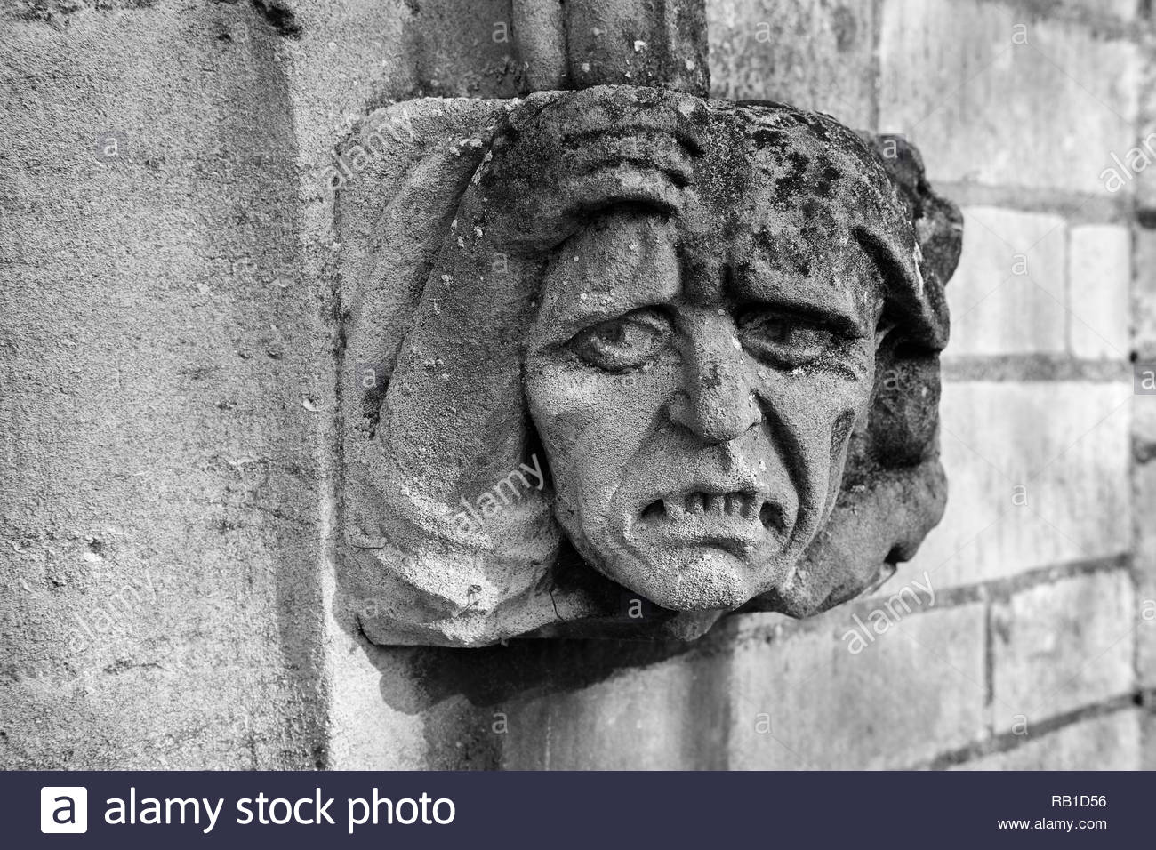 Ecclesiastical sculpture of a grotesque face caved in stone decorating the entrance to a church, Eaton Socon, UK. Stock Photo