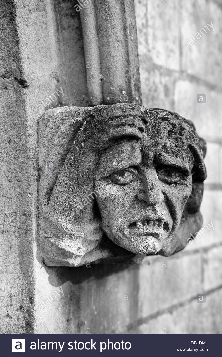 Ecclesiastical sculpture of a grotesque face caved in stone decorating the entrance to a church, Eaton Socon, UK. - Stock Image