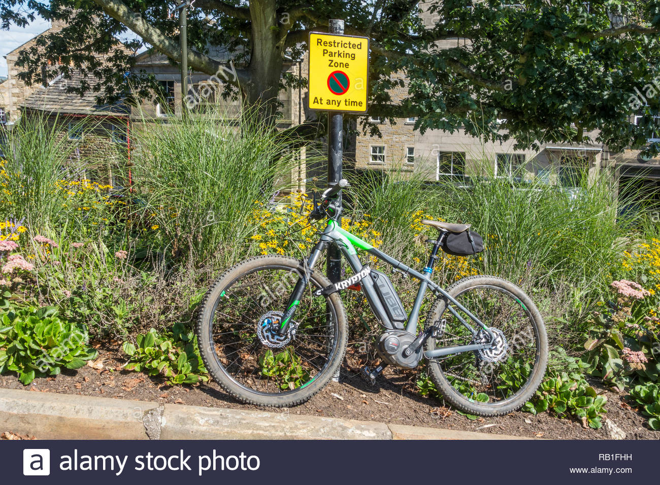 Electric Mountain Bike parked and secured to a post saying Restricted Parking Zone near to the Castle in Lancaster, England, UK - Stock Image