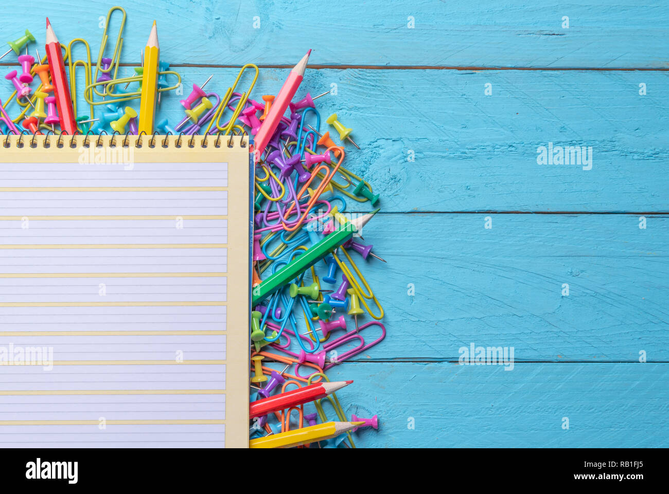 Spiral notebook on a pile of office objects, colored paper clips, crayons and push pins on a blue wooden table - Stock Image