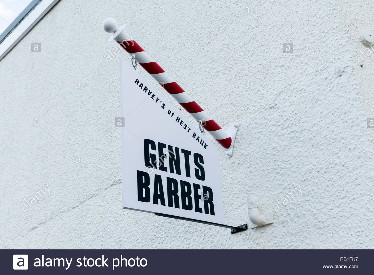 A sign for a gents barber shop with a red and white barber pole in Hest Bank, Lancashire, England, UK - Stock Image