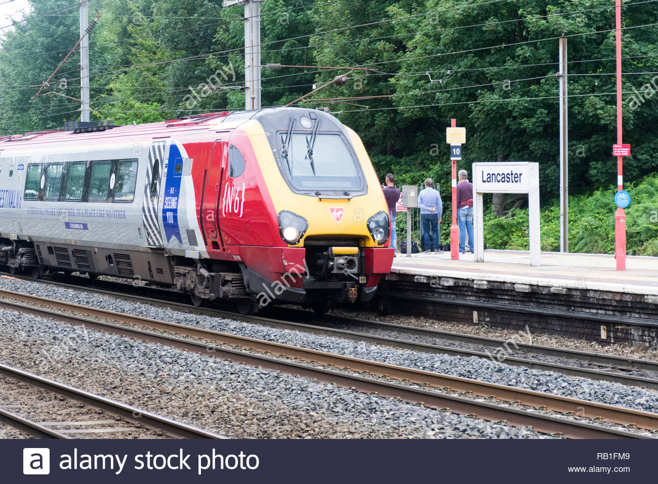 A train heading south and  operated by Virgin Trains pulls into Lancaster Railway Station, Lancashire, England, UK on the West Coast mainline Stock Photo
