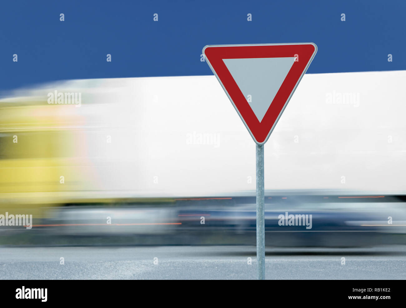 Give way yield road traffic sign, motion blurred white truck in the background, blue summer sky - Stock Image