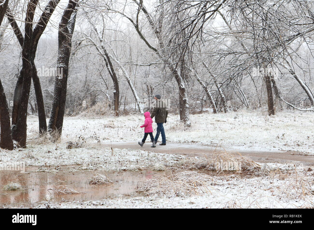 Father and young daughter hiking in the snow - Stock Image
