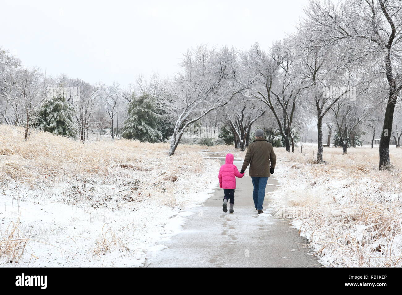 Father and his young daughter walking in a snowy landscape - Stock Image