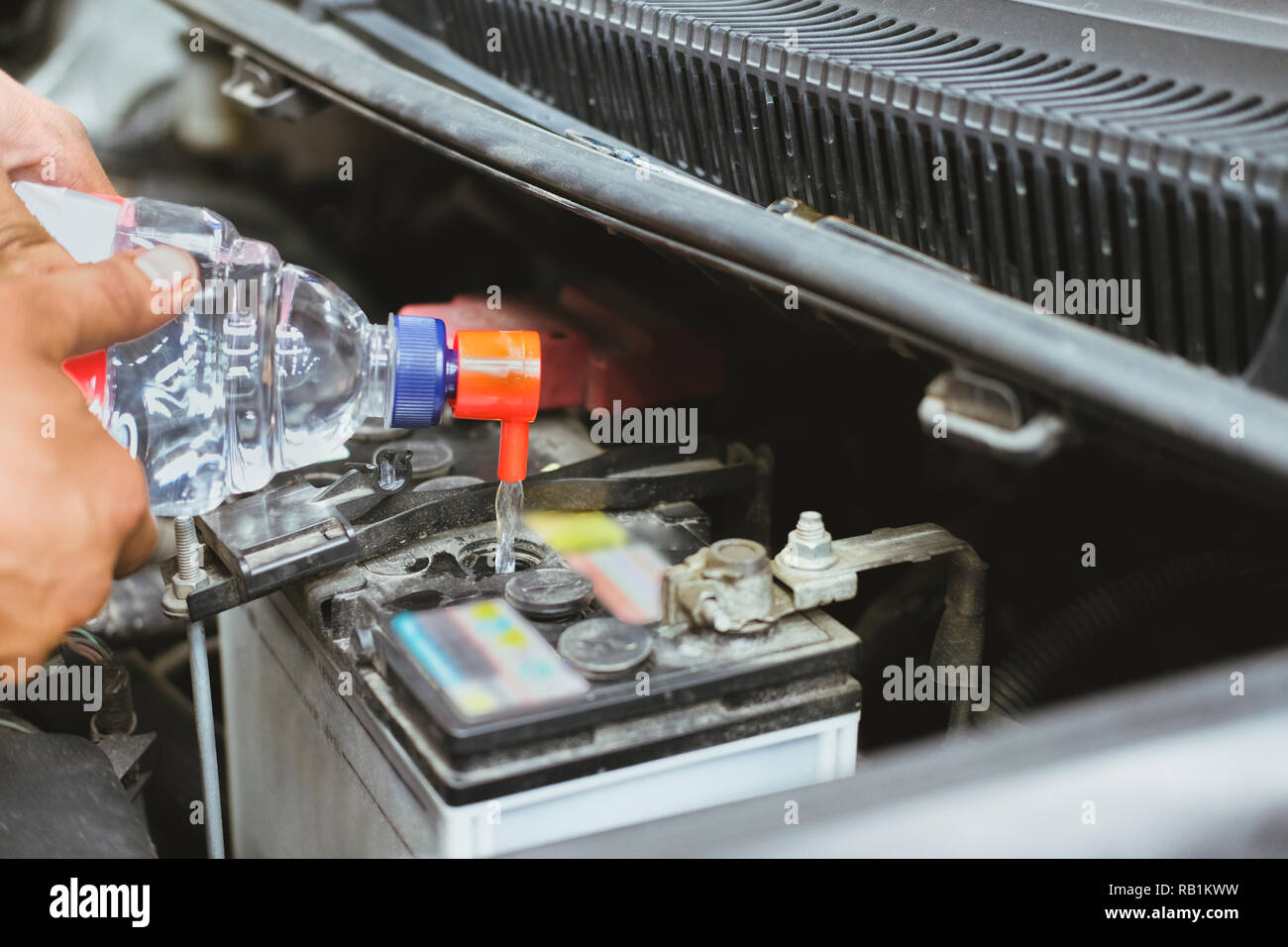 mechanic pouring distilled water to fill car battery in