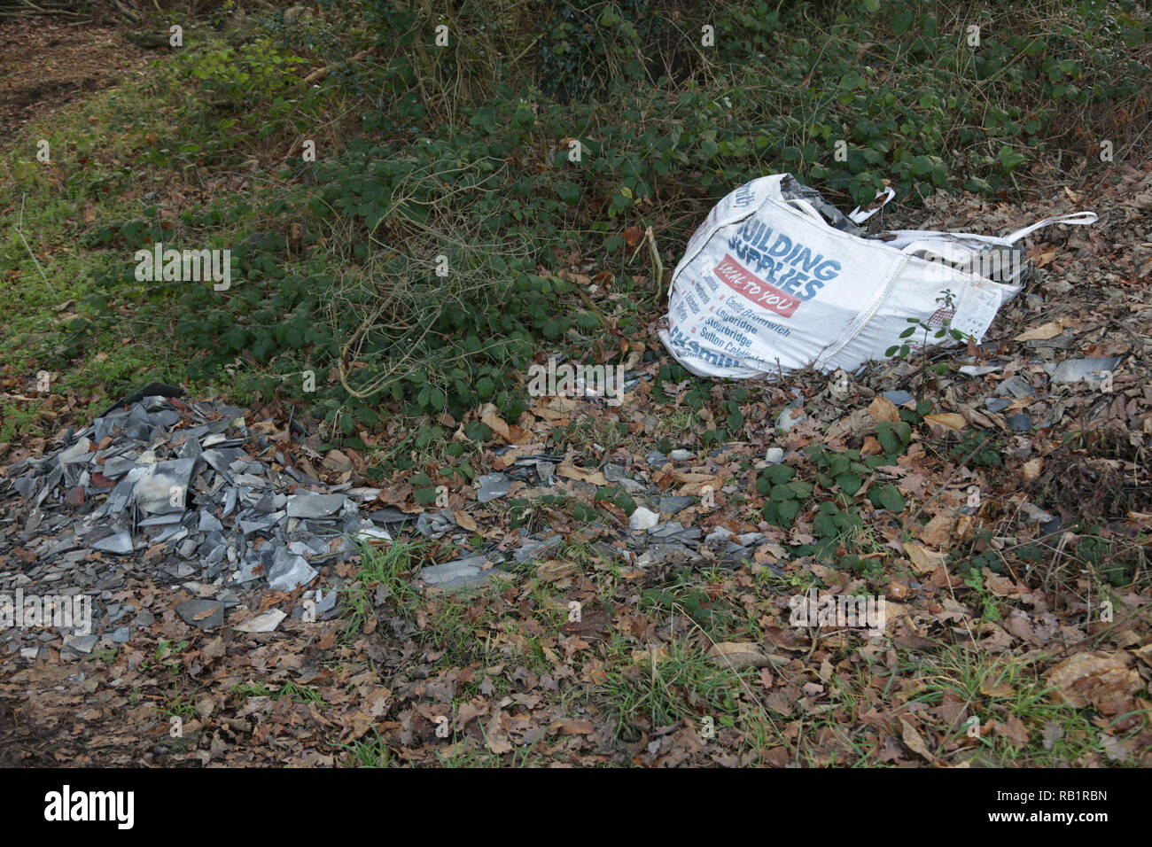 Builders waste dumped in a British country lane. - Stock Image