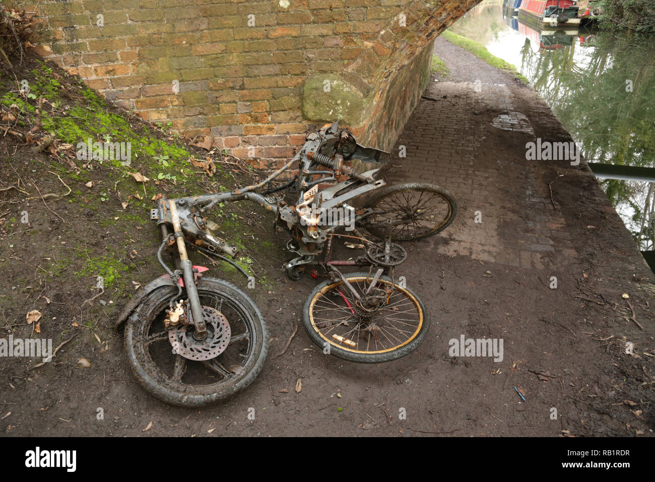 Motorcycle frame and cycle removed from canal and left on towpath, - Stock Image