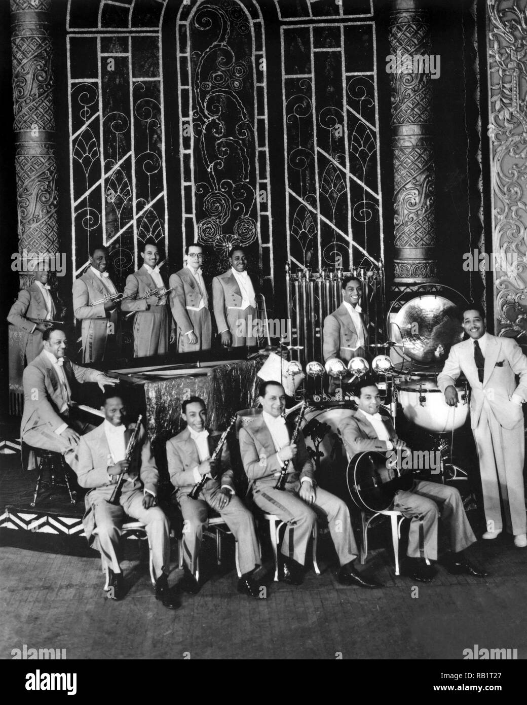 American bandleader and composer Duke Ellington posing with his orchestra on a stage at the Regal Theatre, Chicago. L-R includes: Freddy Jenkins, Wellman Braud, Cotie Williams, Harry Carney, Juan Tizol, Johnny Hodges, Tricky Sam Nanton, Barney Bigard, Sonny Greer, Fred Guy and Ellington. 1931. - Stock Image