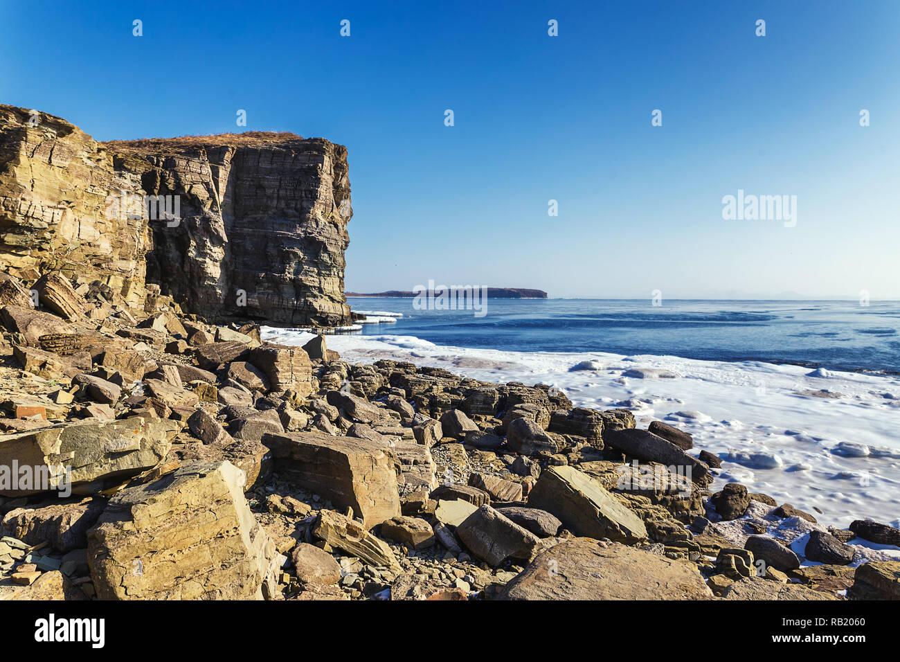 Rocky coast and high cliffs of Tobizin Cape in winter, Vladivostok, Russia - Stock Image