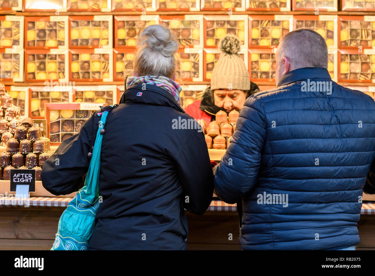 People at Christmas Market stall (potential customers) served by trader, buying chocolates (chocolate teacakes displayed in boxes) - York, England, UK - Stock Image