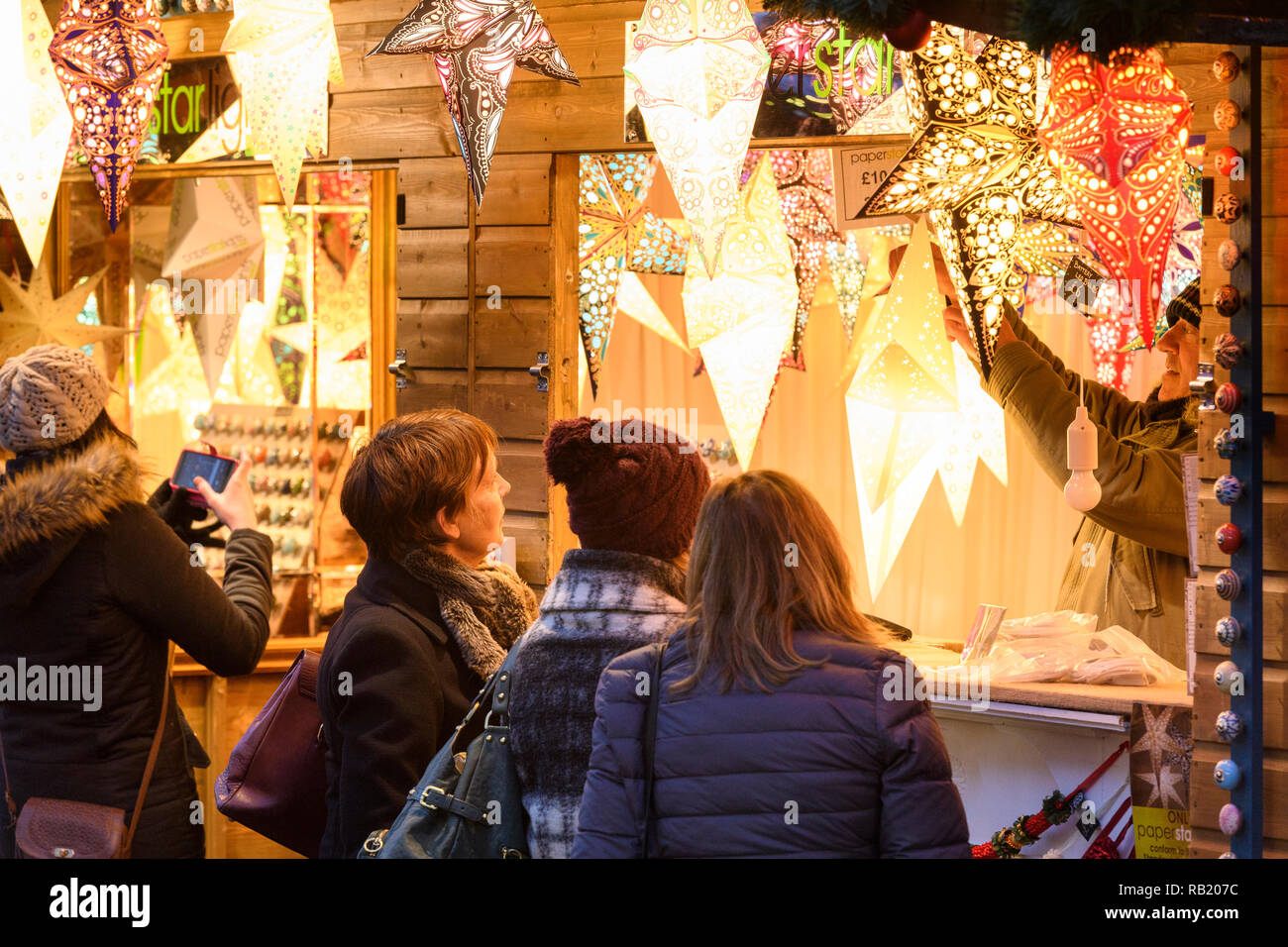 People at Christmas Market stall (potential customers) looking at paper star lights (lanterns) on display casting warm golden glow - York, England, UK - Stock Image