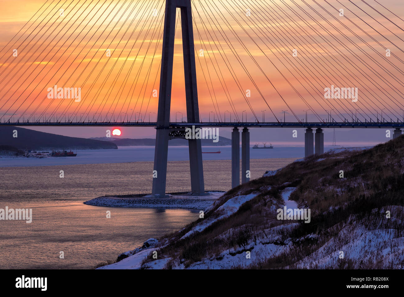 Winter sunset view of long cable-stayed bridge in Vladivostok, Russia - Stock Image