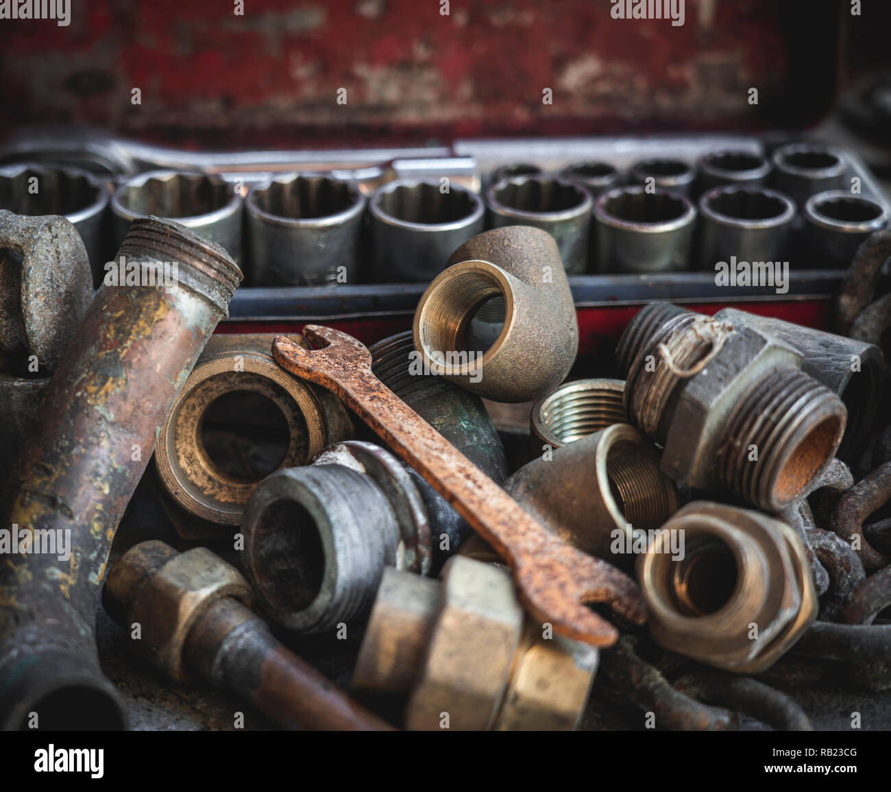 Rusty old plumber pipes with rusty wrench and toolbox. Indsutrial, repair, plumbing and vintage concepts. Stock Photo