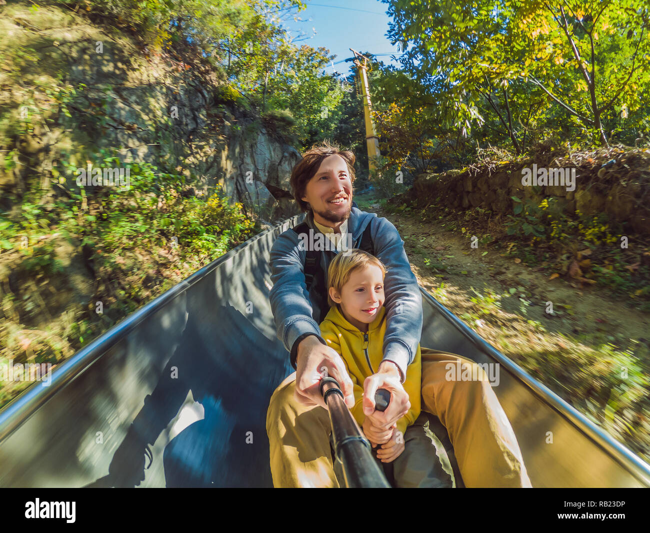 Dad and son have fun on alpine roller coaster - Stock Image