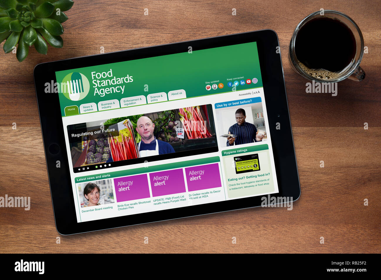 The website of Food Standards Agency is seen on an iPad tablet, on a wooden table along with an espresso coffee and a house plant (Editorial use only) - Stock Image