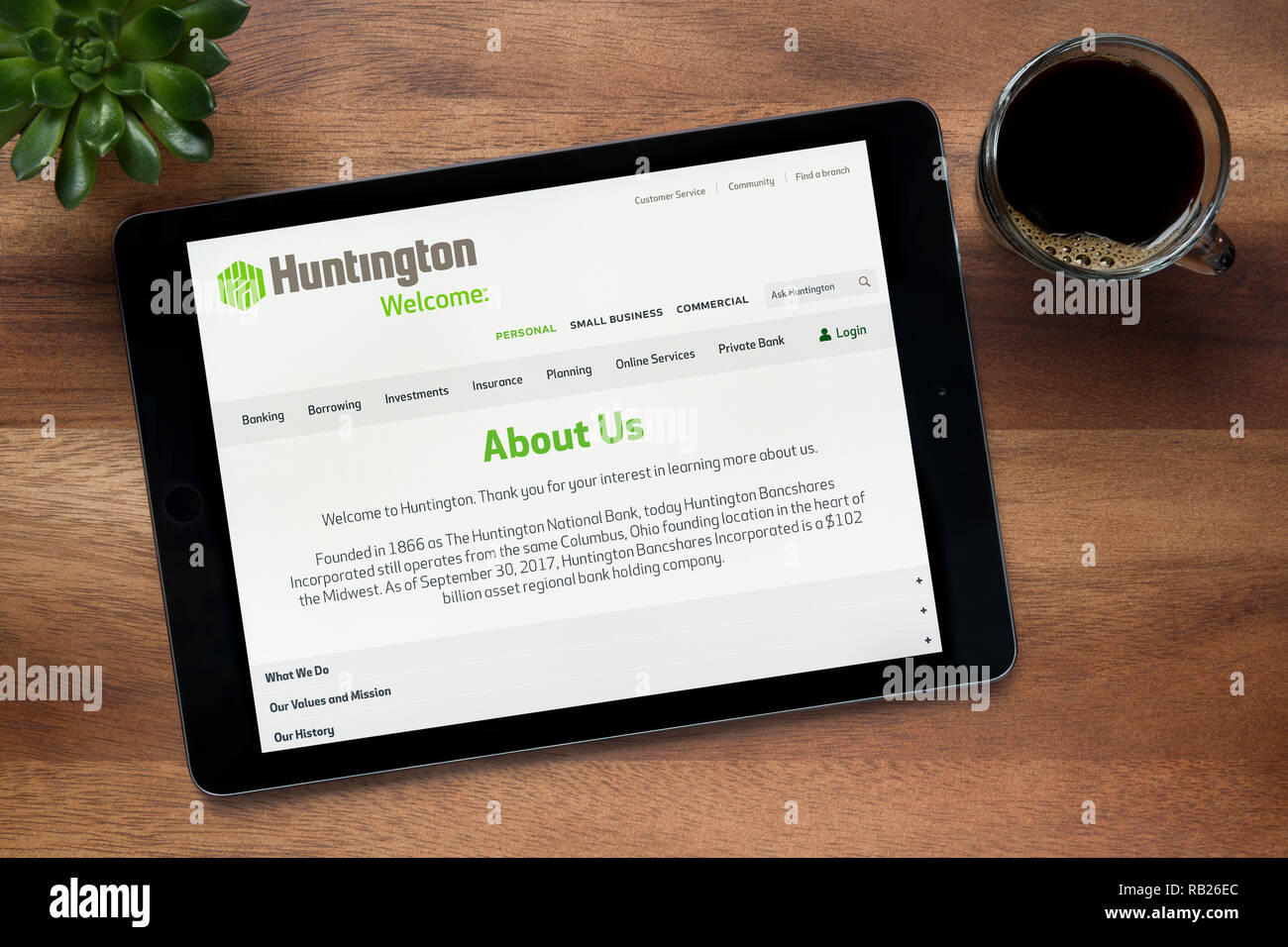 The website of Huntington bank is seen on an iPad tablet, on a wooden table along with an espresso coffee and a house plant (Editorial use only). - Stock Image