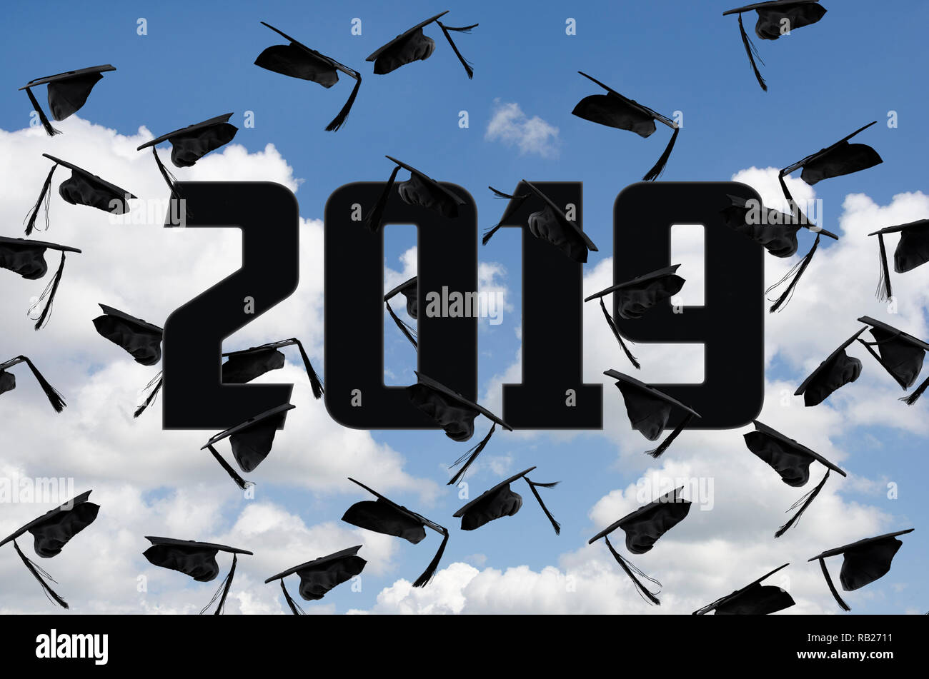 black graduation caps in summer sky with white clouds with year 2019 text - Stock Image