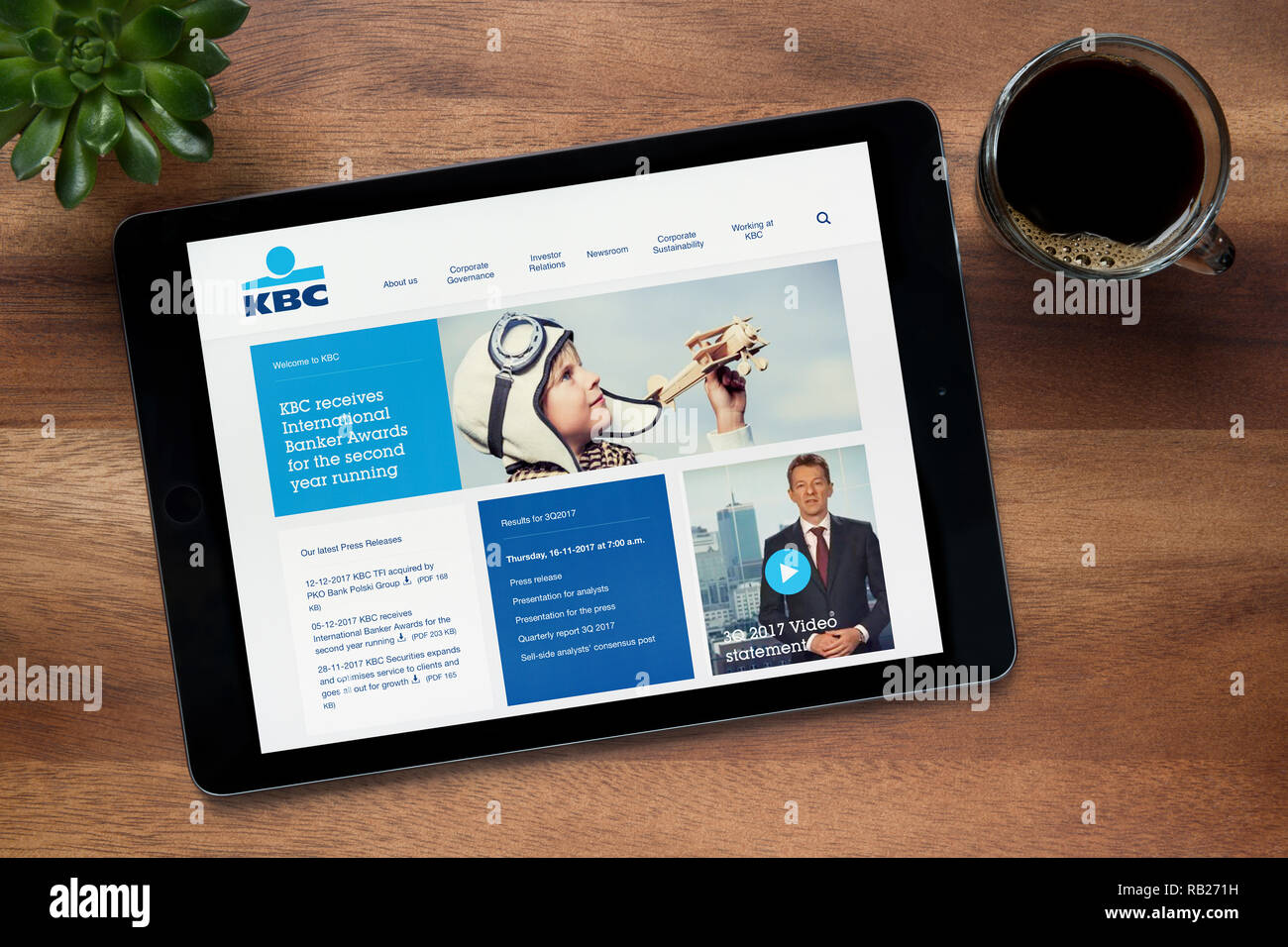 The website of KBC Bank is seen on an iPad tablet, on a wooden table along with an espresso coffee and a house plant (Editorial use only). - Stock Image