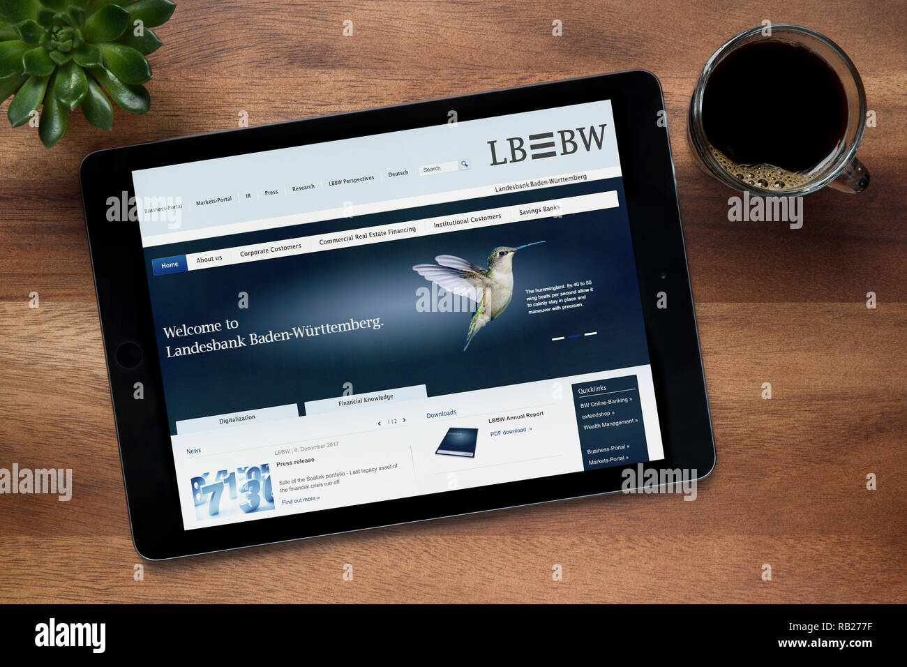 The website of LB BW is seen on an iPad tablet, on a wooden table along with an espresso coffee and a house plant (Editorial use only). - Stock Image